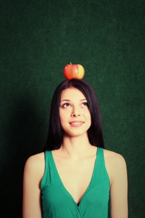 young female with an apple on her head looking up photo