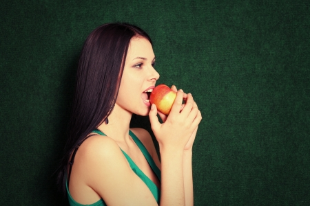 women smiling and bite an apple photo