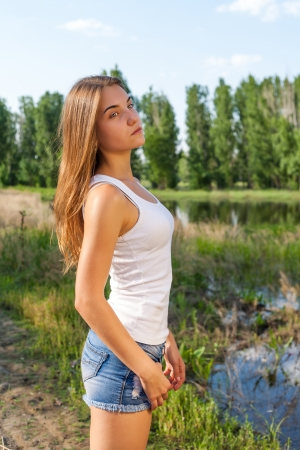 Calm women against lake and forest. Female outdoor torso shot in profile photo