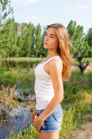 20s female outdoor torso shot in profile. She is weard jeans shorts and looking very cute photo