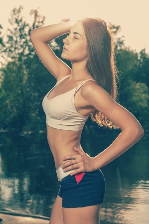 Sporty female outdoors, colorized image, profile view photo