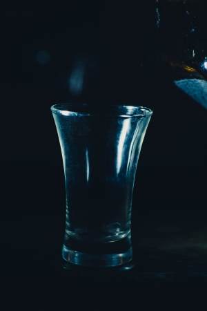bourbon whisky: shot glass on black background