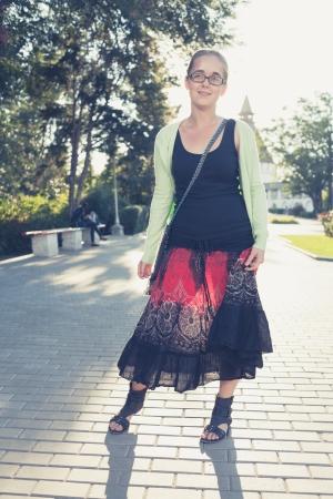 blonde female full body shot standing against sunlight. Backlit photo