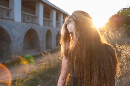citypark: Blonde girl at in sunrise light  Face half hidden by long hair  Citypark with ancient building on background  Backlit with lens flare