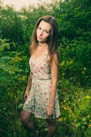 Beautiful Young Woman standing in Meadow of Flowers  Enjoying Nature Stock Photo