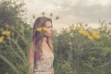 Female in frofile  Beautiful Young Woman standing in Meadow of Flowers  Colorized image  photo