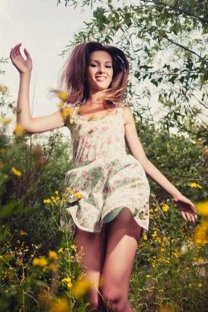 Happy girl dancing outdoors in summer grass