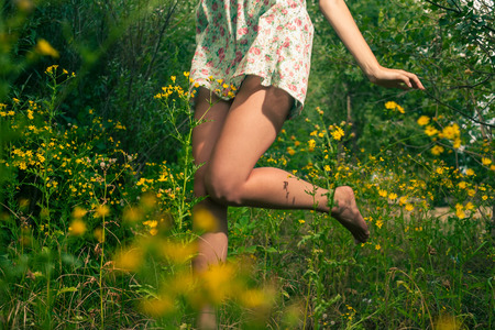 Closeup of the legs of the girl dancing outdoors in summertime photo