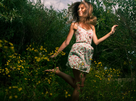 Cute female summertime dance  Happy girl dancing outdoors in grass and flowers photo