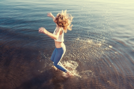 outdoor portrait of young beautiful blonde woman jumping in waves photo