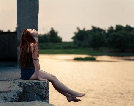 Red haired female looking up profile view  Redhead women sitting near river in summertime and dreaming  Sunset light photo