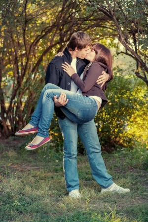 Young happy attractive couple kissing, outdoors