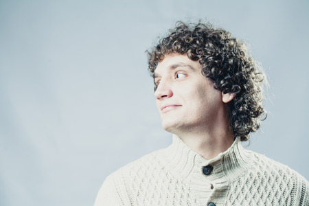 Looking away. Portrait of a young caucasian guy with curly hair photo