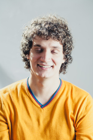 Closed eyes portrait of a young caucasian guy with curly hair photo