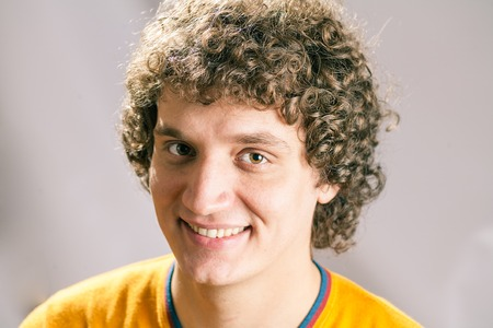 Smiling Curly white man in studio photo