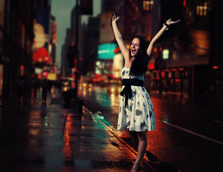Very happy female walking in a NYC street with her hands rised photo