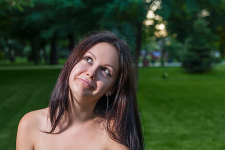 Brunette making facs and looking up (cute grimacing) outdoors photo