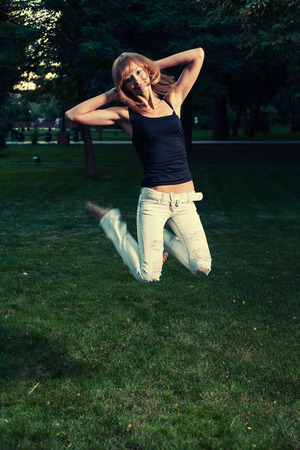Summer fun. Girl in jeans jump on grass photo