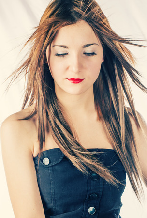 wind down: Magnificient blonde with hair blowing by wind looking down Stock Photo