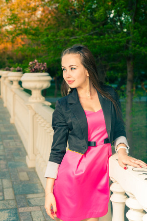 Pretty girl posing alone weared her pink dress photo