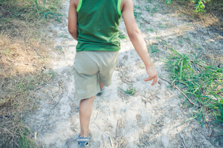 Boy walking in a fores alone. Part of a body shot photo