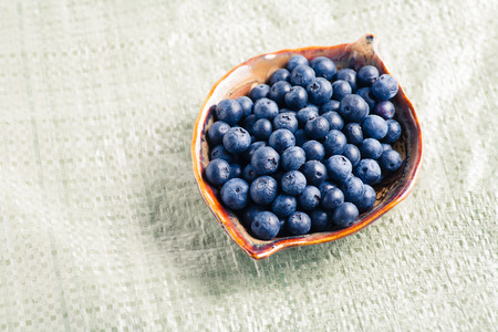colorized: Ripe blueberry in plate on canvas colorized image Stock Photo