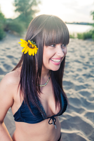 Bikini female with sunflower in her long black hair photo