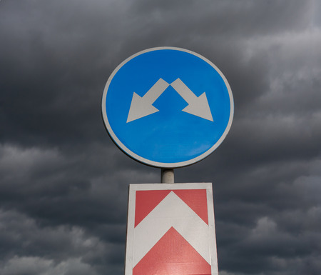 Road sign against cloudy sky square image photo
