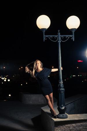 Blonde posing near streetlight at night time photo