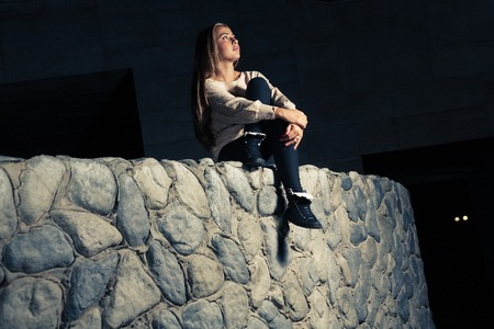 Sporty blonde sitting on a big stone wall and looking up photo