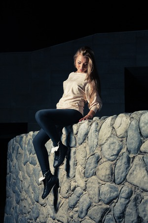 Vertical shot of a pretty girl in sports wear sitting over stone wall outdoors photo