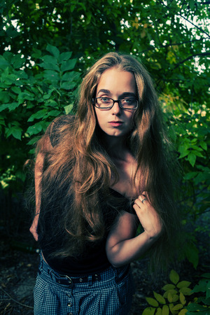 Long haired blonde posing outdoors in glasses photo