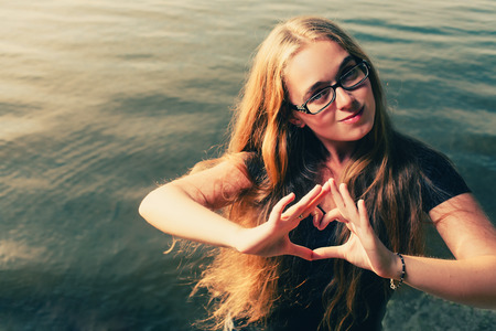 Young blonde makinf heart shape by her hands against water photo