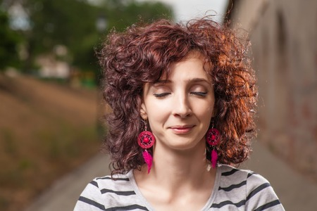 Curly haired women outdoors with her eyes closed. Pretty smile. photo