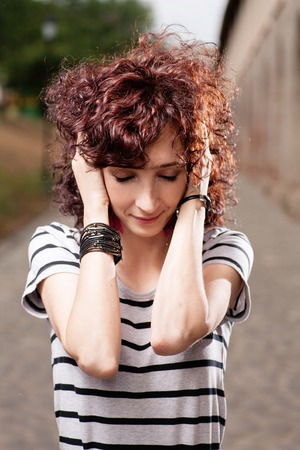 Young beautiful red curly hair woman at the park looking down and holding her head by hands photo