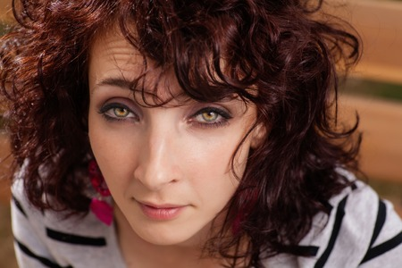 Curly haired female closeup portrait. Red haired women looking at camera photo