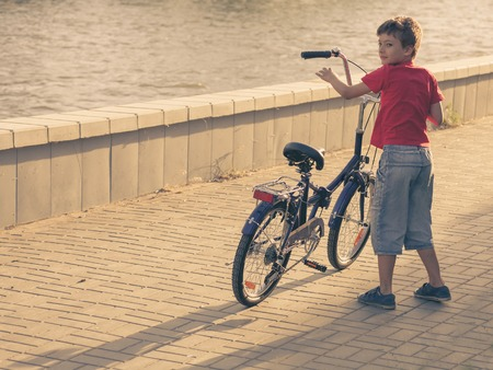 red tshirt: Serious boy riding a bicycle and looking back. Kid in red t-shirt standing hear his bike. Boy with his bicycle from back view. Young boy riding bicycle on a summer day Stock Photo