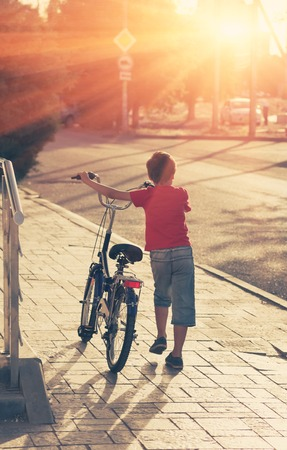 cobblestone street: Little boy with his bike in a street backlit. Young boy riding bicycle on a summer day