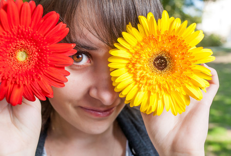 Young woman covering her eyes with fresh colorful flowers. Enjoying spring time. Closeup image photo
