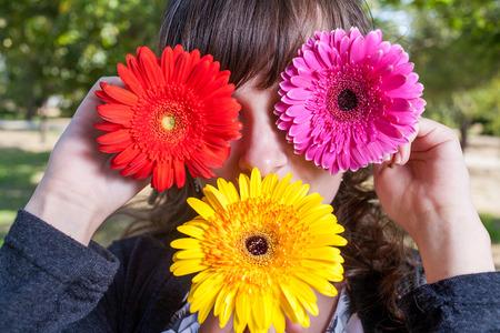 Linda chica ocultar sus ojos y la boca de flores de gerbera photo