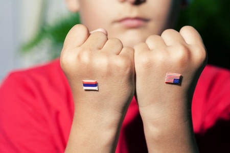 Flag of Russia and Unite States on fist of a boy. World politics concept photo