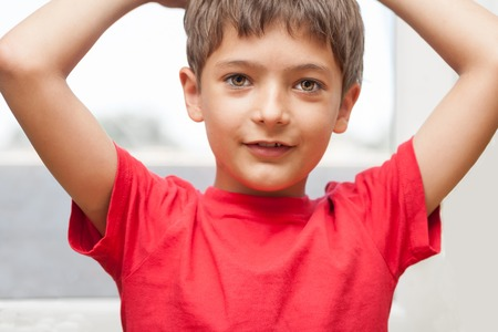 red tshirt: Boy in red t-shirt with his hands up. Stock Photo