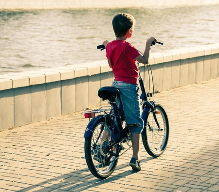 backside: Backside view of a boy on bike near water  Red shirt, jeans shorts