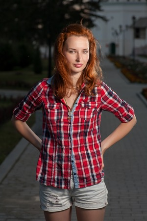 Ginger haired women in jeans shorts and red shirt posing outdoors. Torso shot front view photo