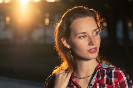 ginger haired: Headshot of ginger haired women backlit. Young beautiful girl at sunset Stock Photo