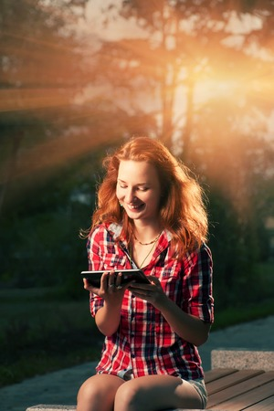 Redhead girl sitting in city park and having fun communicate via tablet PC backlit by sunset photo