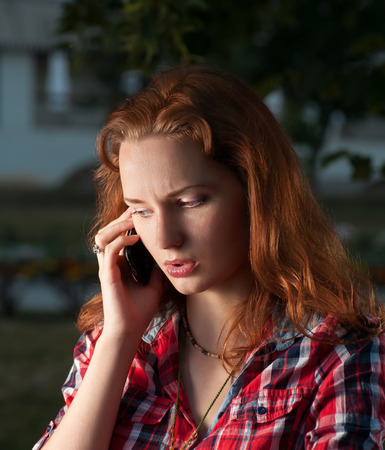 ginger haired: Ginger haired women on cell phone outdoors