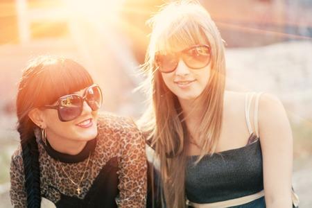 Smiling brunette and blobde women backlit by sunset. photo