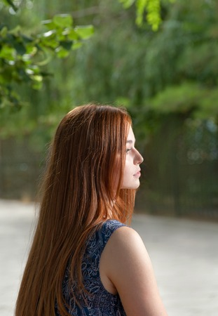 Side view of a red haired women outdoors with blank expression on her pretty face photo
