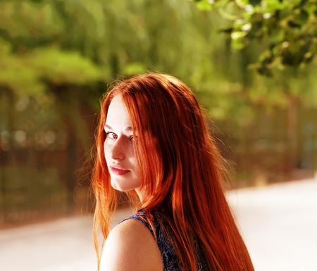 Bright photo of a red haired women in park looking back  photo